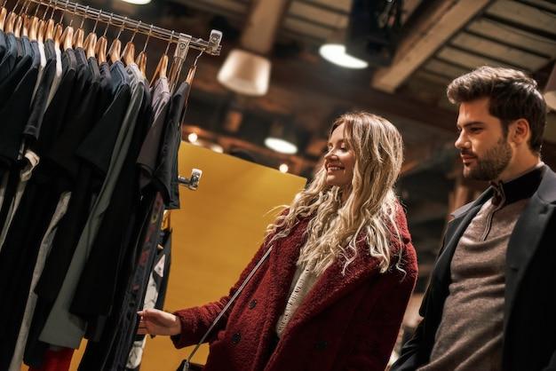 우리는 이 물건을 사야 합니다. 작은 거리 시장에서 수제 드레스를 선택하는 행복한 젊은 부부. 가을 시즌, 그녀의 남자 친구와 금발 머리 여자가 거리 시장에 있습니다