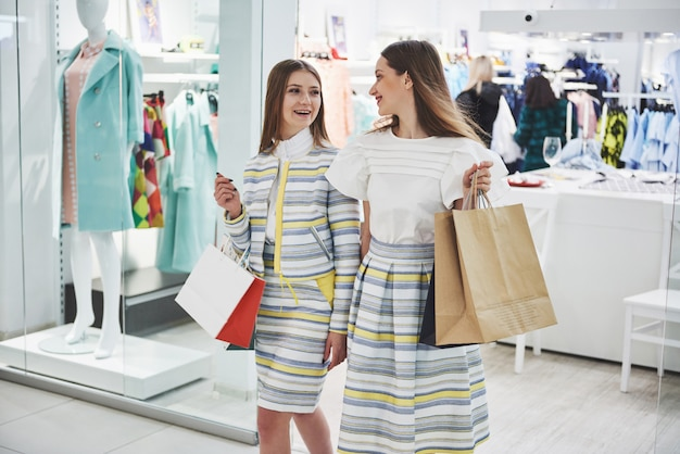 We should look at new dresses rear view of two beautiful women with shopping bags looking away with smile while walking at the clothing store