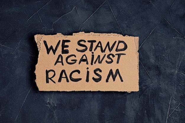 私たちは暗い背景の上の段ボールの人種差別的なテキストに反対します