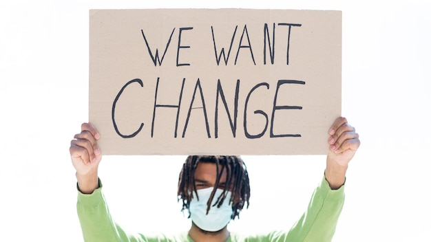 We want change quote on cardboard held by young person