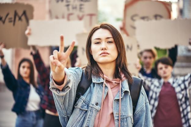 Мы хотим мира, молодая женщина показывает знак фигуры, стоя перед женщиной