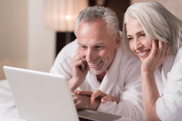 우리는 영화를보고 있습니다. 기쁨을 표현하면서 침대에 누워 노트북에서 영화를보고 기쁘게 웃는 세 커플