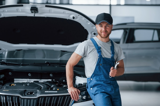 We will fix anything. employee in the blue colored uniform stands in the automobile salon