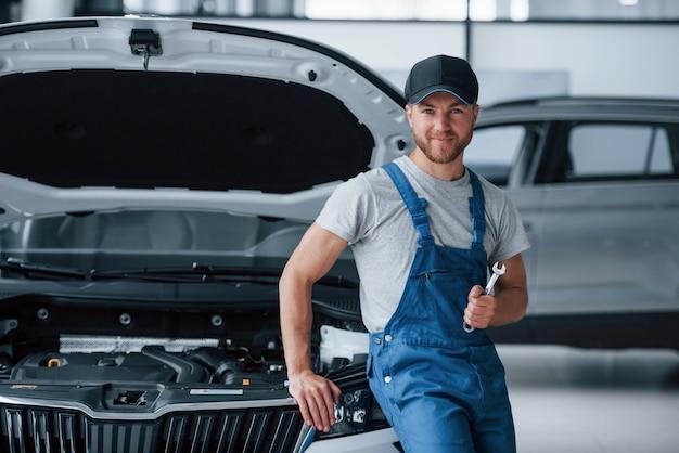 Мы все исправим. сотрудник в синей форме стоит в автомобильном салоне