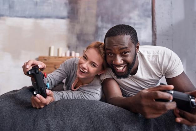 Мы победим. концентрированная молодая пара из разных стран наслаждается рекламой игр с помощью консоли, лежа в постели.
