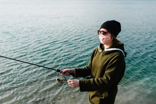 Covid-19を獲得しました。湖のほとりにスピニングリールを持つ漁師。田舎での検疫の概念。