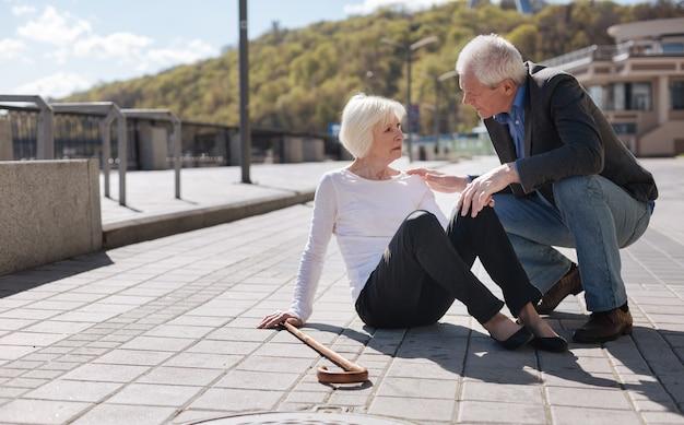 Слабая старая приятная женщина с сильной болью в теле и просящая о помощи, пока добрый прохожий ее слушает