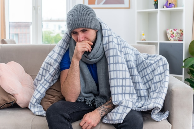 스카프와 겨울 모자를 쓰고 약하고 아픈 젊은 아픈 남자는 입에 손을 대고 아래를 내려다 보면서 거실에서 소파에 앉아 담요에 싸여 있습니다.