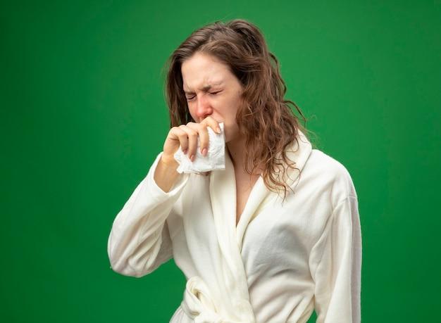 緑で隔離の口に手を置いてナプキンを保持している白いローブを着て弱い咳の若い病気の女の子