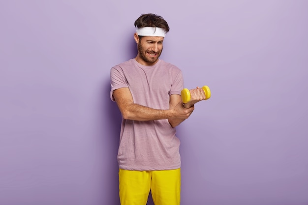 Weak man tries to lift heavy dumbbell, wants to be strong and fit, does exercises regularly, dressed in t shirt and yellow shorts