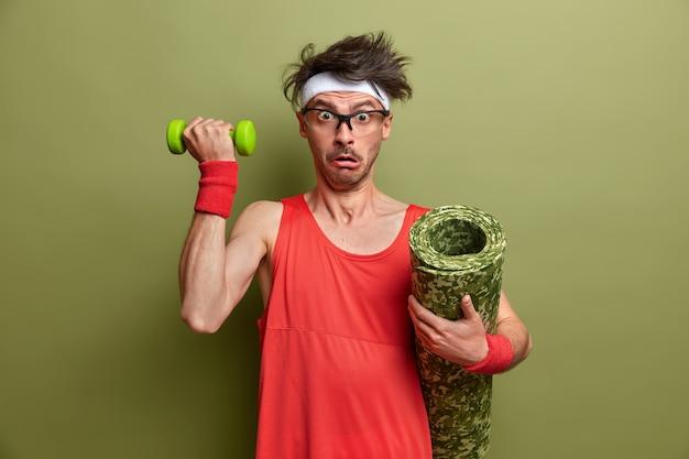 L'uomo debole vuole diventare bodybuilder, alza le braccia con il manubrio, scioccato da quanto sia pesante, tiene il karemat sotto l'ascella, vestito con abiti sportivi rossi, isolato sul muro verde. uno stile di vita sano