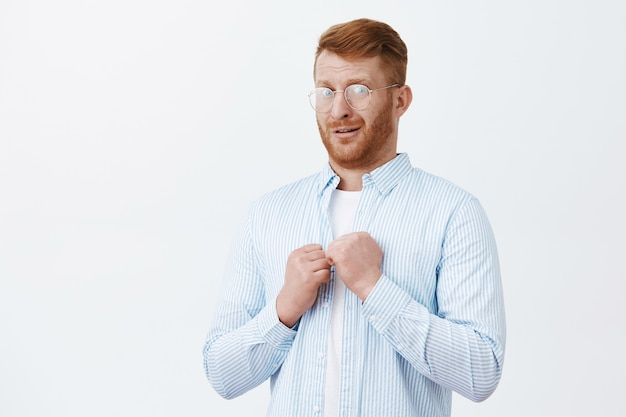 透明な眼鏡とシャツを着た弱い成熟した赤毛の男、不確かに握りこぶしを上げ、眉をひそめ、心配して強烈に見つめ、灰色の壁に殴られるのを怖がる