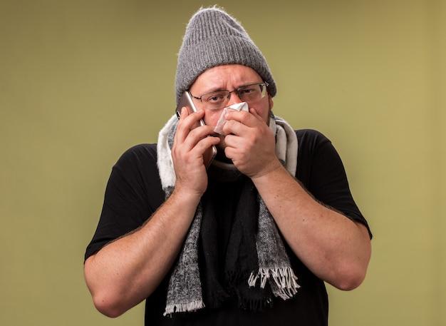 冬の帽子とスカーフを身に着けている弱い中年の病気の男性は、オリーブグリーンの壁に分離されたナプキンで鼻を拭く電話で話します