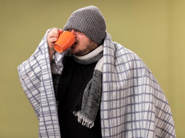 オリーブグリーンの壁に隔離されたカップから格子縞の飲み物のお茶に包まれた冬の帽子とスカーフを身に着けている弱い中年の病気の男性