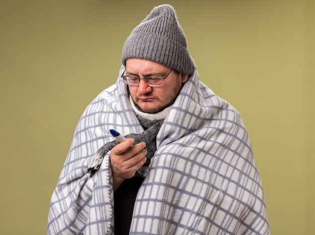 冬の帽子とスカーフを身に着けている弱い中年の病気の男性は、格子縞の保持に包まれ、オリーブグリーンの壁に隔離された温度計を見ています