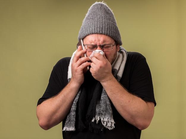 Debole maschio malato di mezza età che indossa cappello invernale e sciarpa parla al telefono asciugandosi il naso con un tovagliolo isolato sulla parete verde oliva