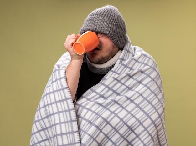 Debole maschio malato di mezza età che indossa un cappello invernale e una sciarpa avvolta in un plaid beve il tè dalla tazza isolata su una parete verde oliva
