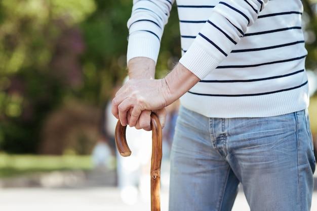 공원에서 날씨를 즐기면서 서서 막대기에 기대어 약한 평화로운 노인