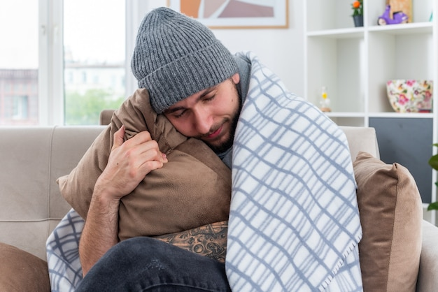 Weak and pleased young ill man wearing scarf and winter hat sitting on sofa in living room wrapped in blanket hugging pillow resting head on it with closed eyes