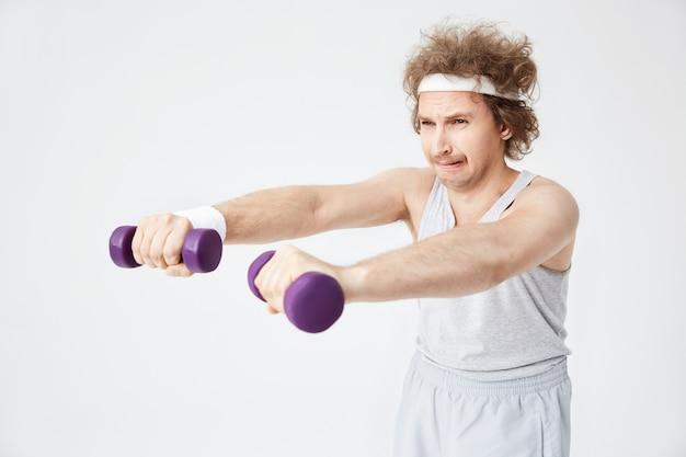 昔ながらのスポーツウェアの弱いレトロな男がハードトレーニング