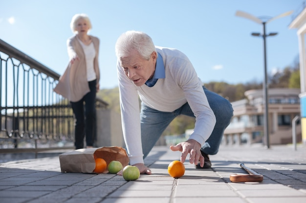 Weak startled senior man feeling sickness and dropping fruits while kind woman looking at him