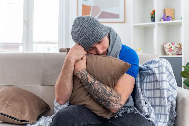 Debole e stanco giovane uomo malato che indossa sciarpa e cappello invernale seduto sul divano in soggiorno abbracciando cuscino appoggiando la testa su di esso con gli occhi chiusi