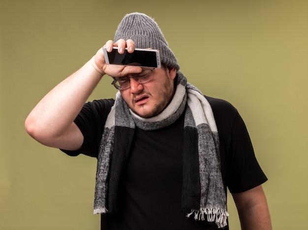 目を閉じて弱い冬の帽子とスカーフを身に着けている中年の病気の男性は、オリーブグリーンの壁に隔離された手で額を拭く電話を保持しています