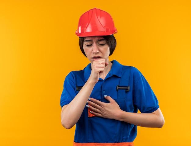 Debole con gli occhi chiusi giovane donna del costruttore in uniforme che tossisce isolata sulla parete gialla con lo spazio della copia
