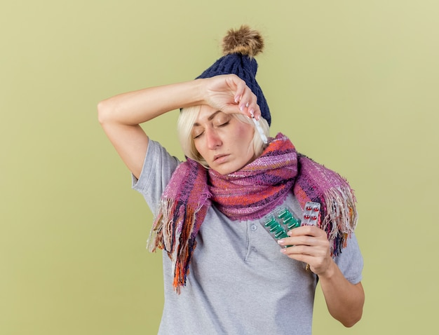 겨울 모자와 스카프를 착용하는 약한 젊은 금발의 아픈 슬라브 여자는 이마에 손을 넣고 복사 공간이 올리브 녹색 벽에 고립 된 의료 약 팩을 보유하고 있습니다.