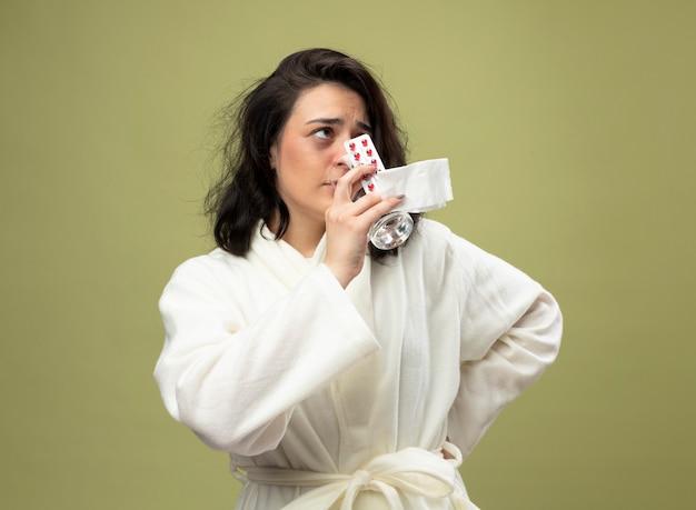 Слабая молодая кавказская больная девушка в халате, держащая упаковку медицинских таблеток, стакан воды и салфетку с питьевой водой, держа руку на талии, глядя в сторону, изолированную на оливково-зеленом фоне