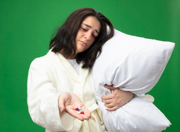 Debole giovane indoeuropea ragazza malata indossando accappatoio tenendo il cuscino che allunga capsule mediche verso la telecamera guardando capsule isolate su sfondo verde