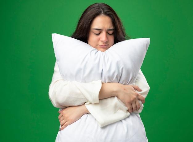 녹색 배경에 고립 된 닫힌 눈을 가진 가운 포옹 베개를 입고 약한 젊은 백인 아픈 소녀