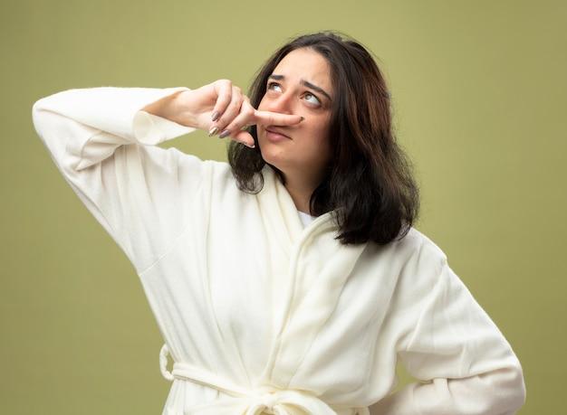 Слабая молодая кавказская больная девушка в халате, держащая руку на талии, вытирая нос, глядя вверх изолированно на оливково-зеленом фоне