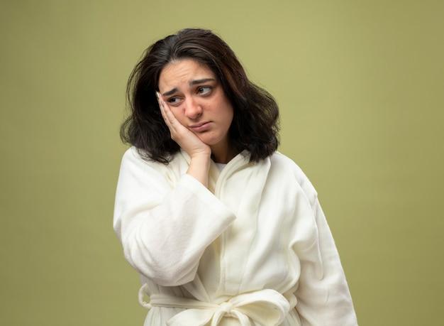 Debole giovane indoeuropea ragazza malata che indossa veste mettendo la mano sul viso guardando il lato isolato su sfondo verde oliva con spazio di copia