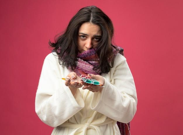 Debole giovane ragazza malata caucasica che indossa veste e sciarpa tenendo la siringa e confezioni di capsule mediche guardando la telecamera isolata su sfondo cremisi con spazio di copia