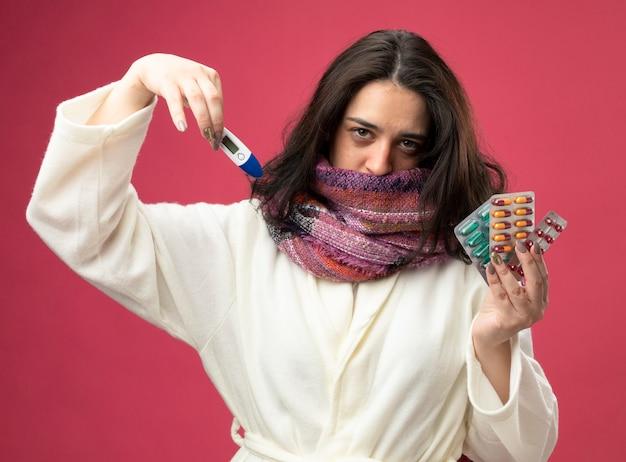 Debole giovane caucasica ragazza malata che indossa accappatoio e sciarpa che mostra confezioni di capsule mediche e termometro guardando la telecamera isolata su sfondo cremisi