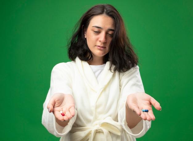 Debole giovane ragazza malata caucasica che indossa un abito che allunga le capsule mediche verso la telecamera con gli occhi chiusi isolati su priorità bassa verde