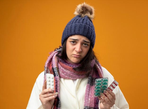 オレンジ色の背景に分離されたカメラを見て、ローブの冬の帽子と医療薬のパックを保持しているスカーフを身に着けている弱い若い白人の病気の女の子