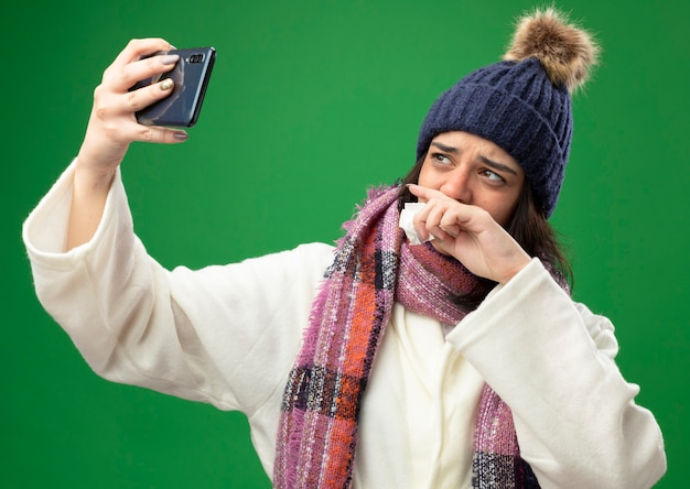 Weak young caucasian ill girl wearing robe winter hat and scarf holding napkin keeping hand on mouth taking selfie isolated on green background