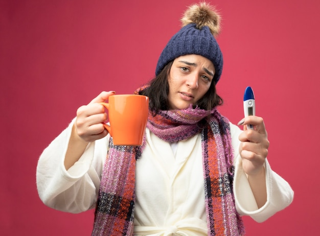 Debole giovane ragazza malata caucasica indossando il cappello invernale veste e sciarpa che allunga fuori la tazza di tè e che tiene il termometro isolato sulla parete cremisi