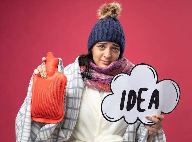 Debole giovane ragazza caucasica malata che indossa un cappello invernale e sciarpa avvolti in plaid che tiene borsa dell'acqua calda e bolla idea isolata sul muro cremisi
