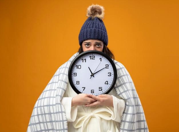 オレンジ色の背景で隔離の後ろからカメラを見て格子縞の保持時計に包まれたローブの冬の帽子を身に着けている弱い若い白人の病気の女の子