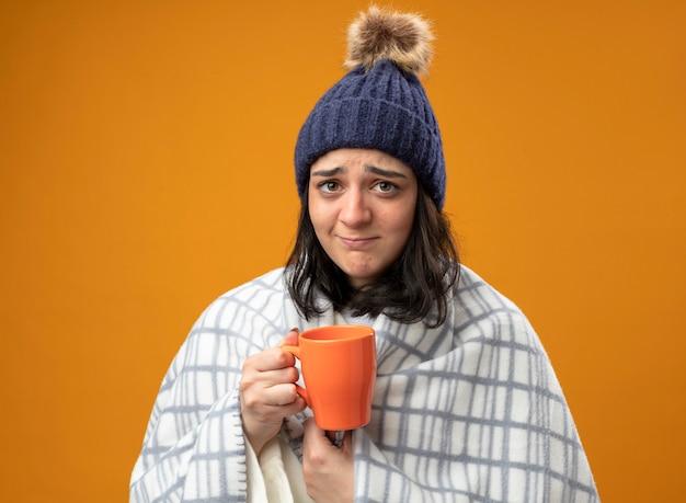 Debole giovane caucasica ragazza malata che indossa un abito invernale cappello avvolto in plaid tenendo la tazza di tè guardando la telecamera isolata su sfondo arancione