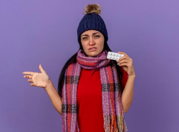 겨울 모자와 스카프를 착용하는 약한 젊은 백인 아픈 소녀 복사 공간이 보라색 배경에 고립 된 손으로 측면을 가리키는 카메라를보고 정제의 팩을 보여주는