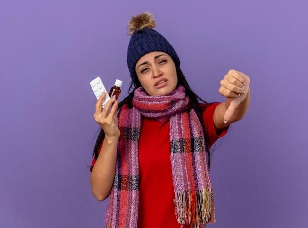 Debole giovane ragazza malata caucasica che indossa cappello invernale e sciarpa che tiene medicamento in vetro e confezione di compresse che mostra il pollice verso il basso isolato sulla parete viola con spazio di copia