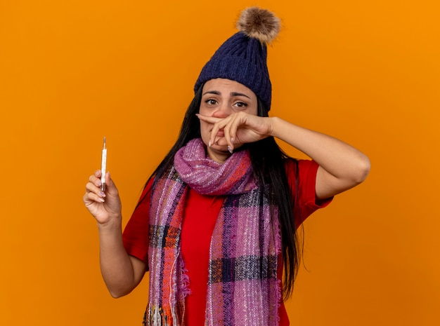 Debole giovane ragazza malata caucasica che indossa cappello invernale e sciarpa tenendo il termometro asciugandosi il naso isolato sulla parete arancione