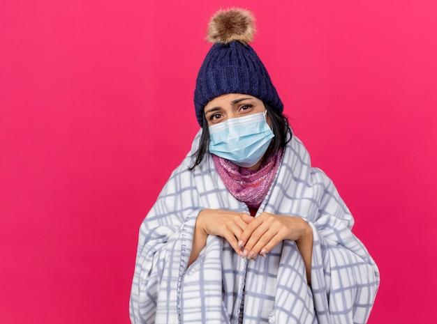 Debole giovane ragazza malata caucasica che indossa cappello invernale e sciarpa con maschera avvolta in un plaid che guarda l'obbiettivo tenendo le mani insieme isolato su sfondo cremisi con spazio di copia