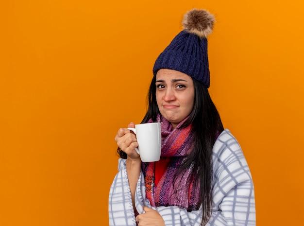 Debole giovane ragazza malata caucasica che indossa cappello invernale e sciarpa avvolto in una tazza di tè della holding del plaid che guarda l'obbiettivo isolato su priorità bassa arancione con lo spazio della copia