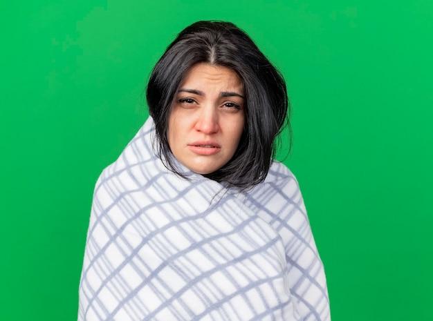 コピースペースで緑の背景に分離されたカメラを見て格子縞に包まれた弱い若い白人の病気の女の子
