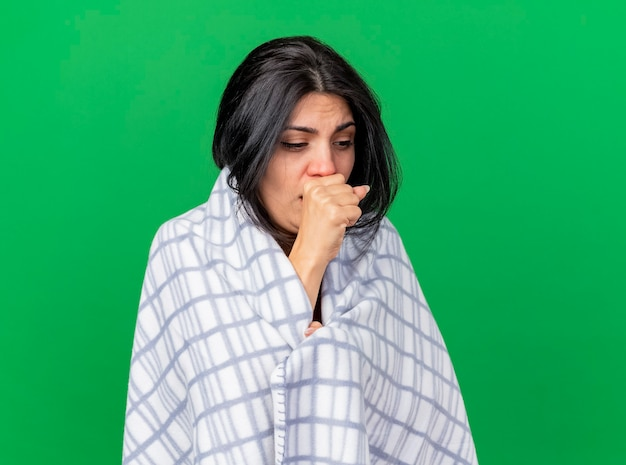 Weak young caucasian ill girl wrapped in plaid coughing keeping fist on mouth looking down isolated on green background with copy space